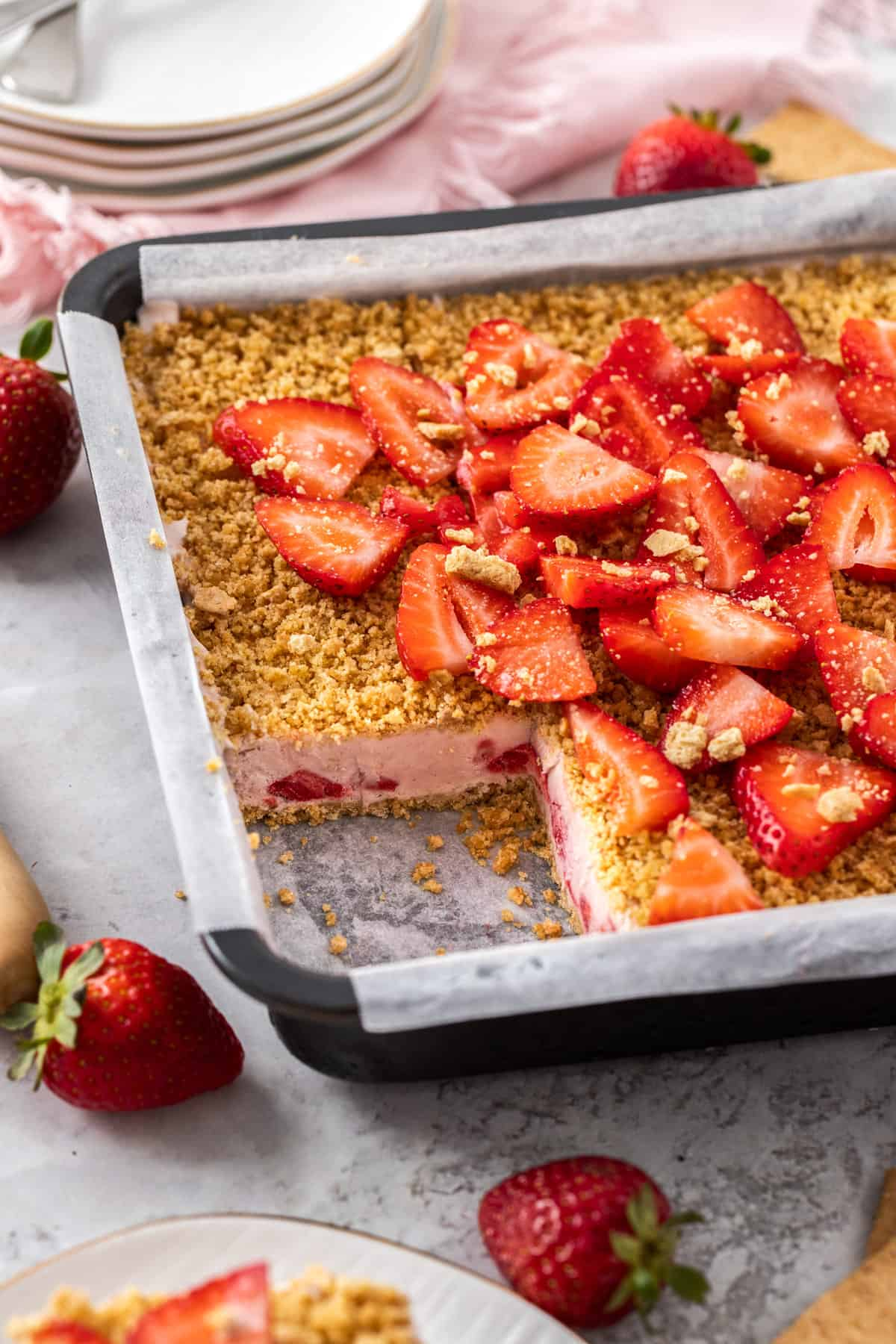 strawberry dessert in pan with square serving cut out