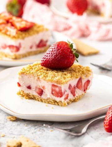frozen strawberry dessert on a plate topped with a whole strawberry