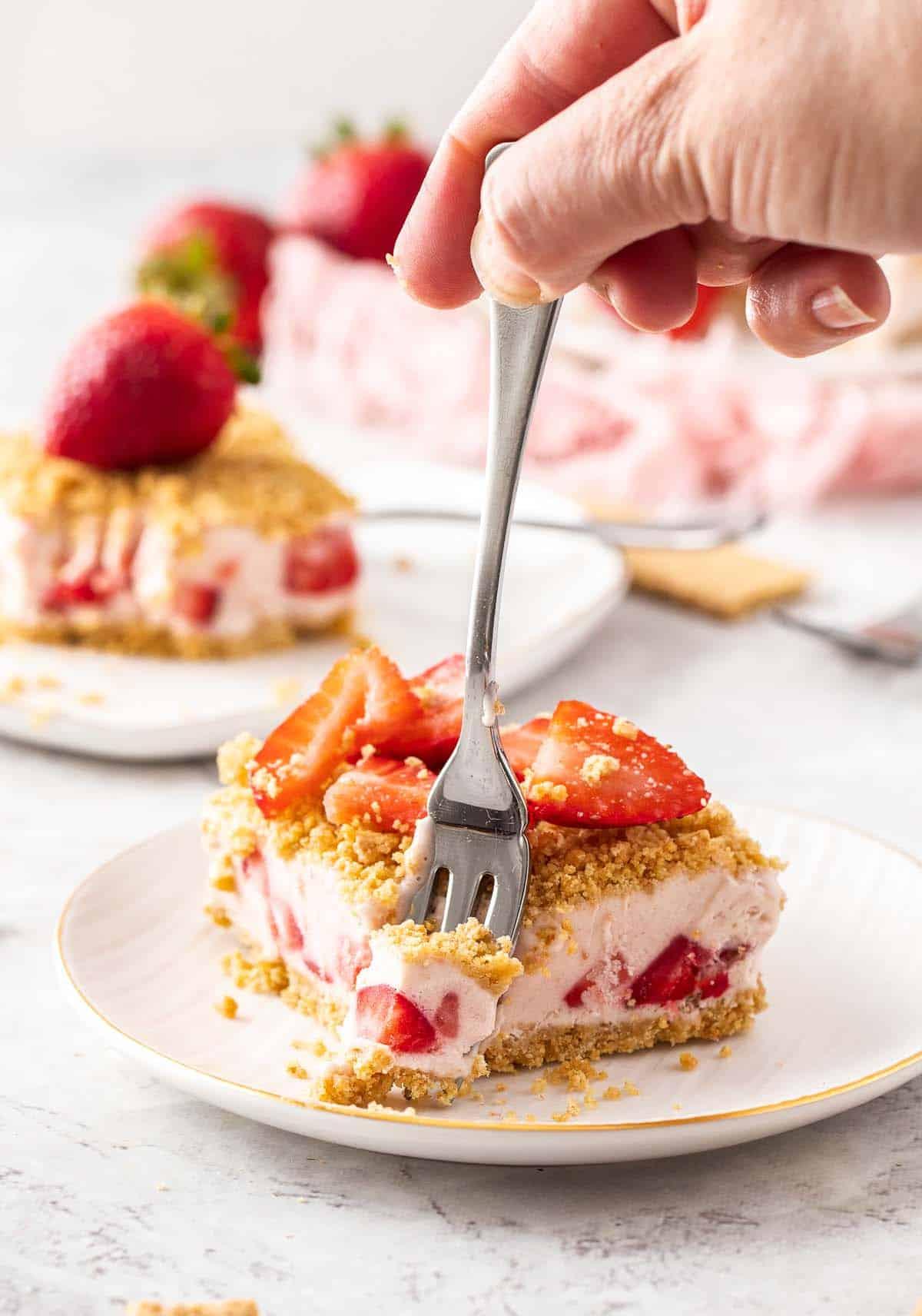 hand holding fork in strawberry dessert
