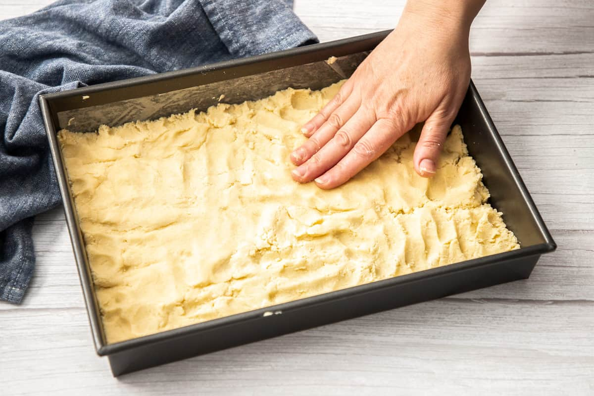 pressing cookie dough into pan