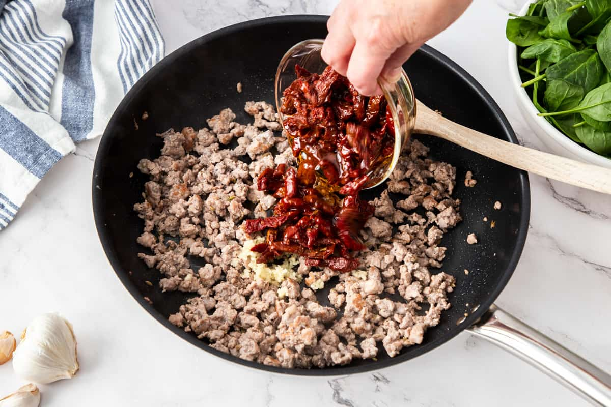 pouring sundried tomatoes into pan with cooked sausage
