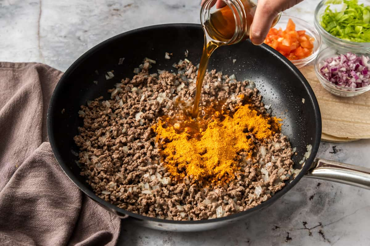 ground beef in skillet with taco seasoning for taco pie