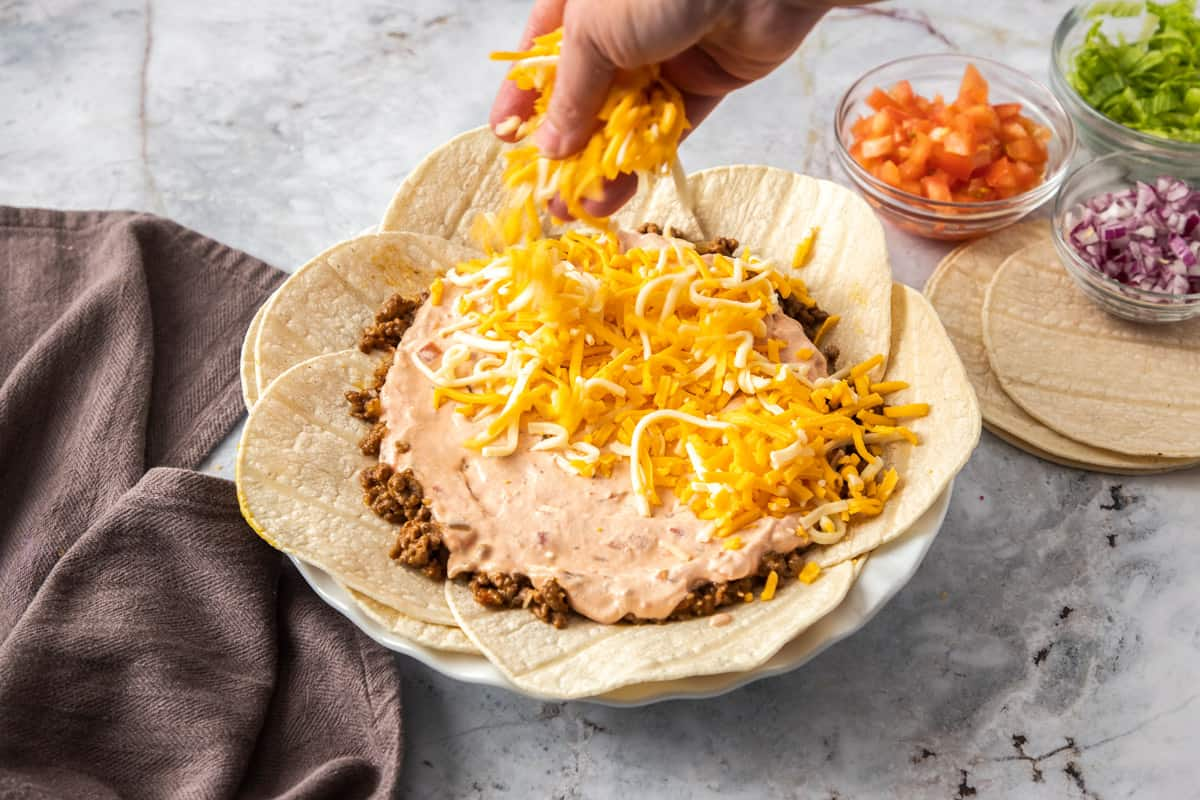 layered tortillas and meat and cheese for taco pie