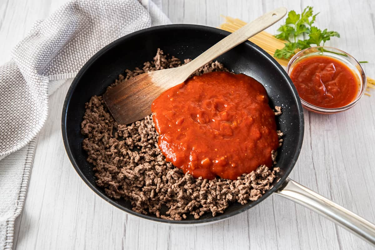 cooked beef in skillet with pasta sauce for baked spaghetti recipe