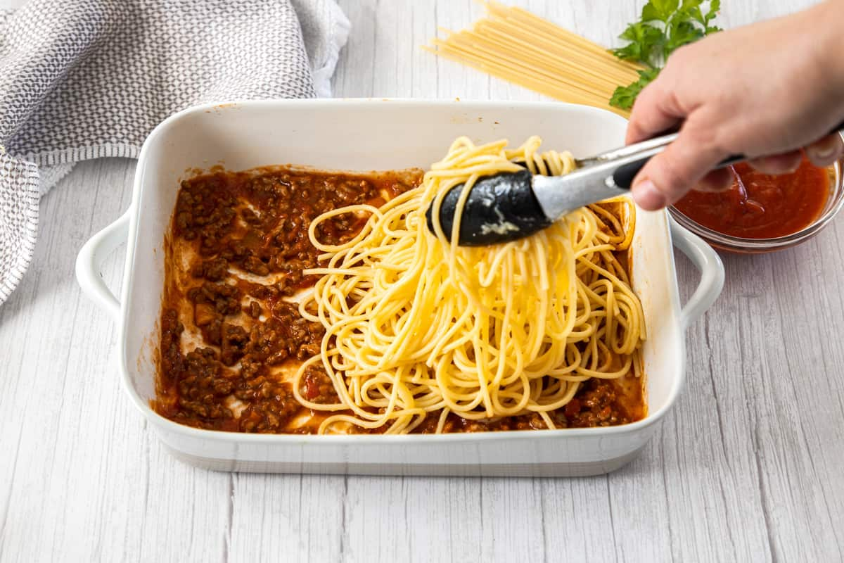 pasta and spaghetti layered into baking pan