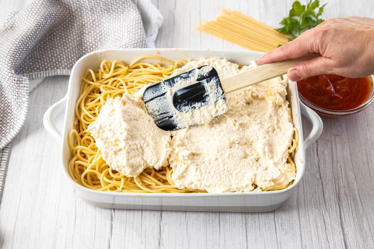 spreading ricotta into pan over spaghetti noodles