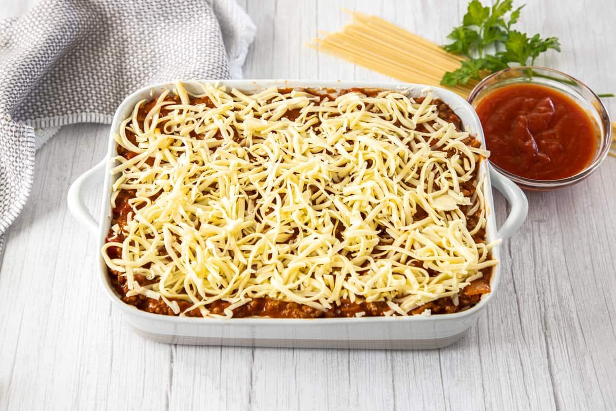 shredded mozzarella over pan of spaghetti